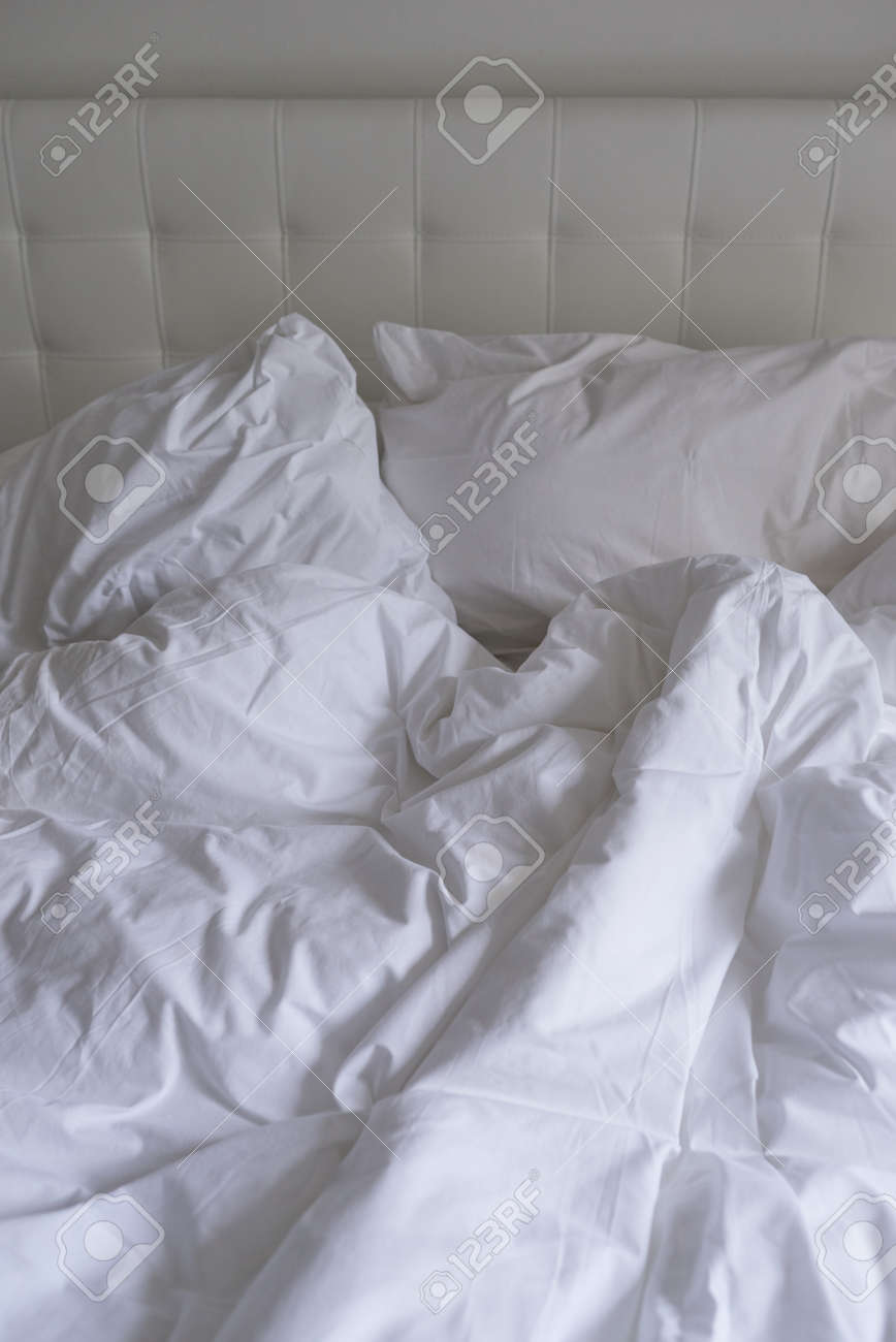 Unmade Bed With Plain White Bed Linen In A Close Up View Of A
