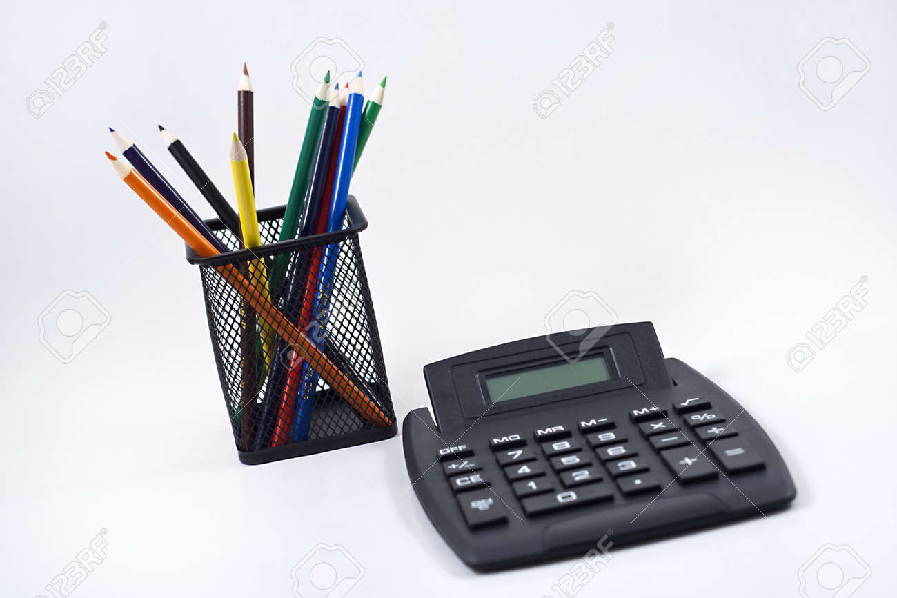 Color pencils in black pencil holder and calculator on white background. Stock Photo - 10506793