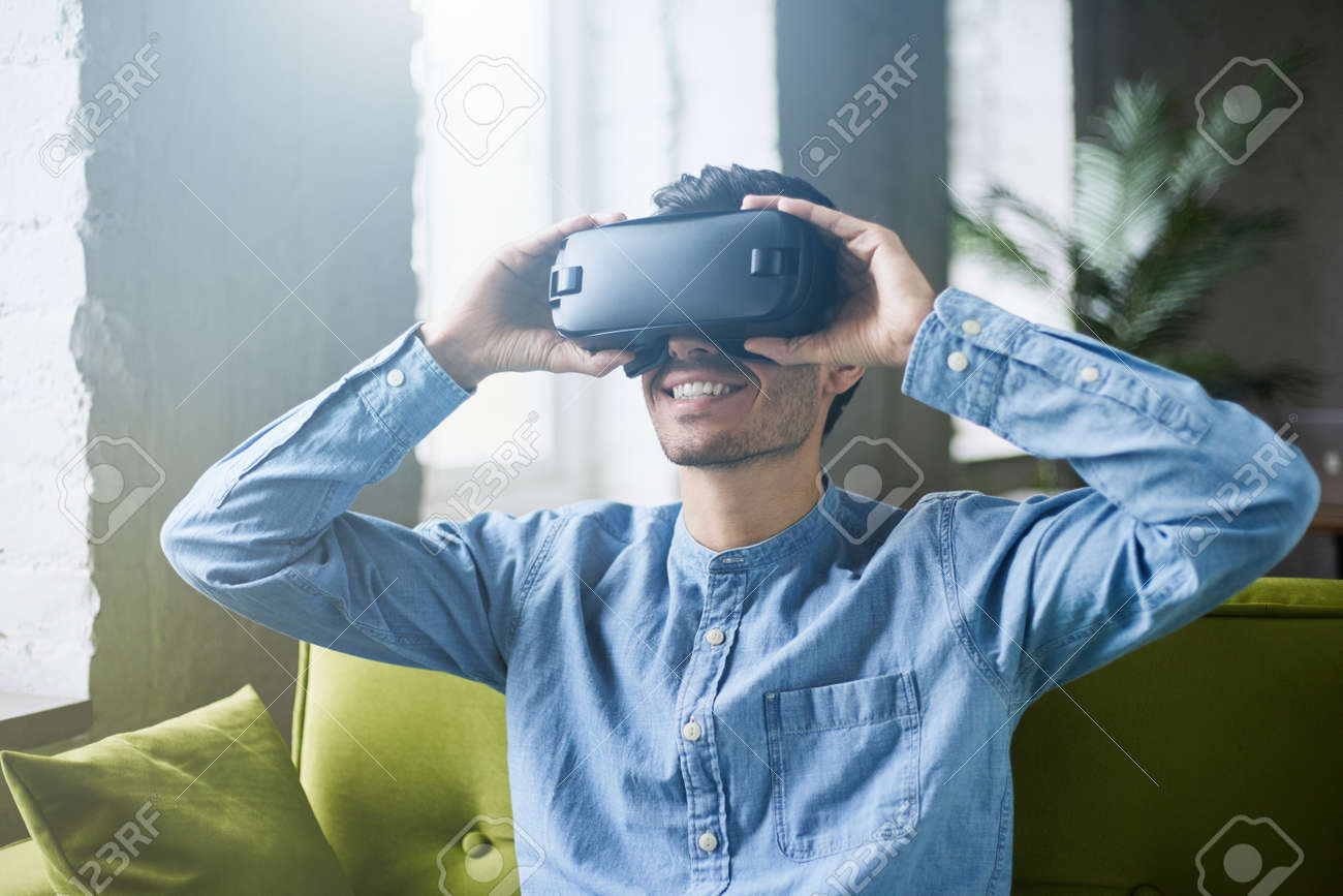 acf9be33461 Attractive young man in blue denim shirt wearing virtual reality headset or  3d glasses sitting on green sofa at home. Handsome caucasian male using VR  ...