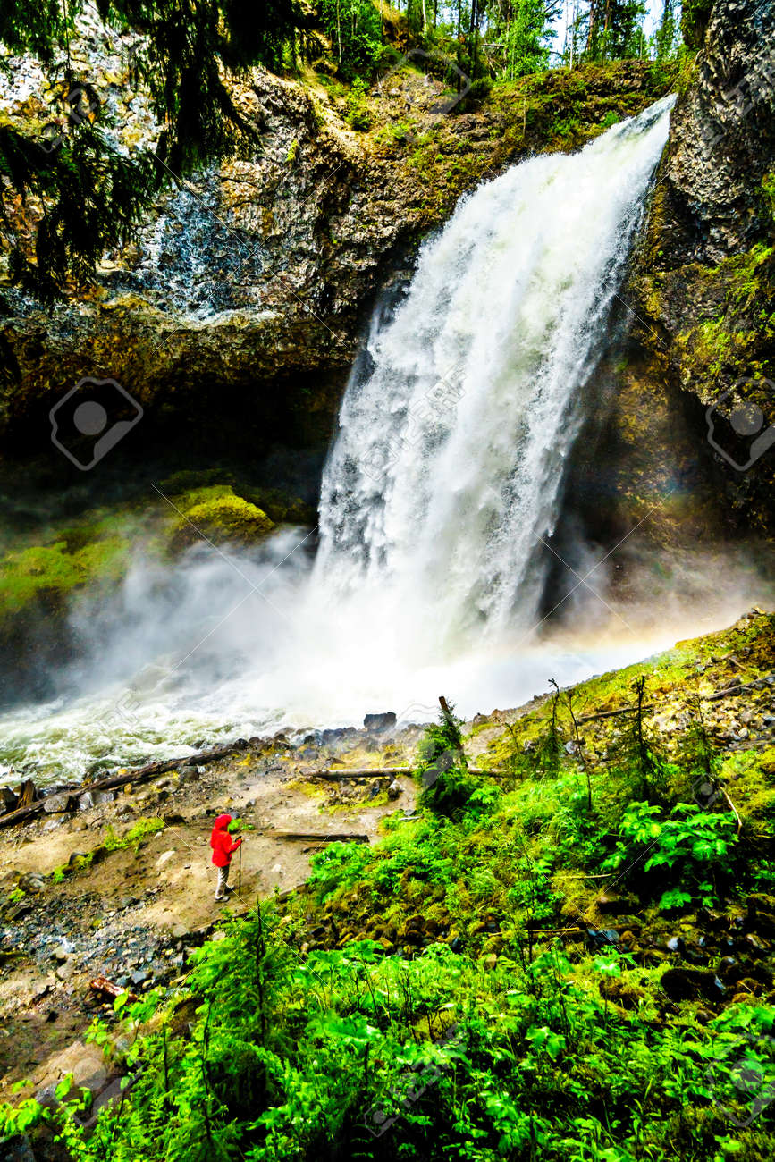 Woman in a Wind Breaker in the mist at the bottom of Moul Falls,