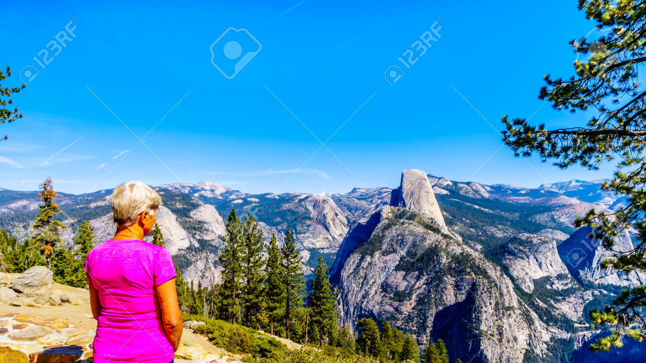 Senior Woman enjoying the view from Glacier Point at the end of Glacier Point Road of the Sierra Nevada high country, with the curved tooth of the famous Half Dome in the foreground in Yosemite National Park, California, USA - 136071939
