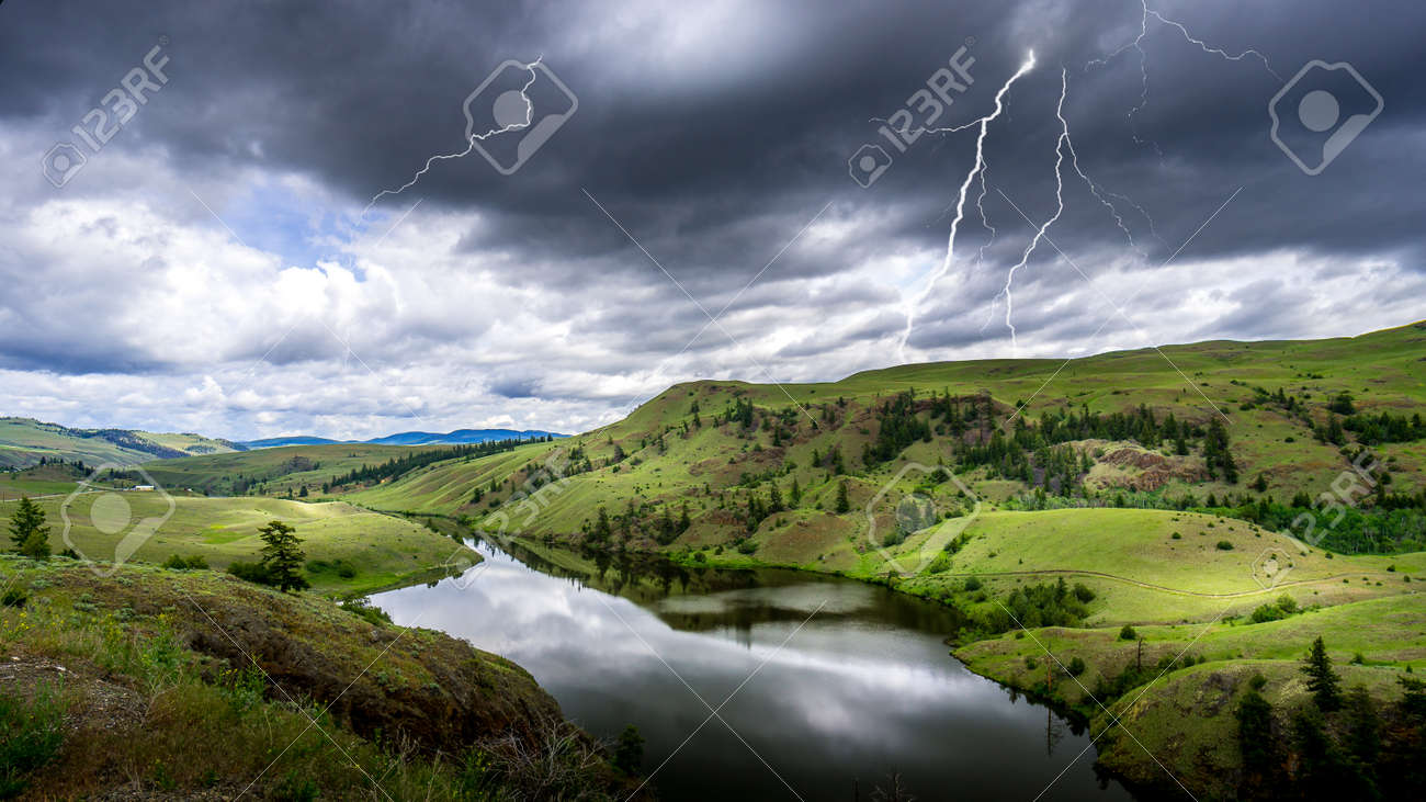 Lightning Strikes from Dark Clouds over Napier Lake in the Grasslands along Highway 5A between Kamloops and Merritt in British Columbia, Canada - 156121220