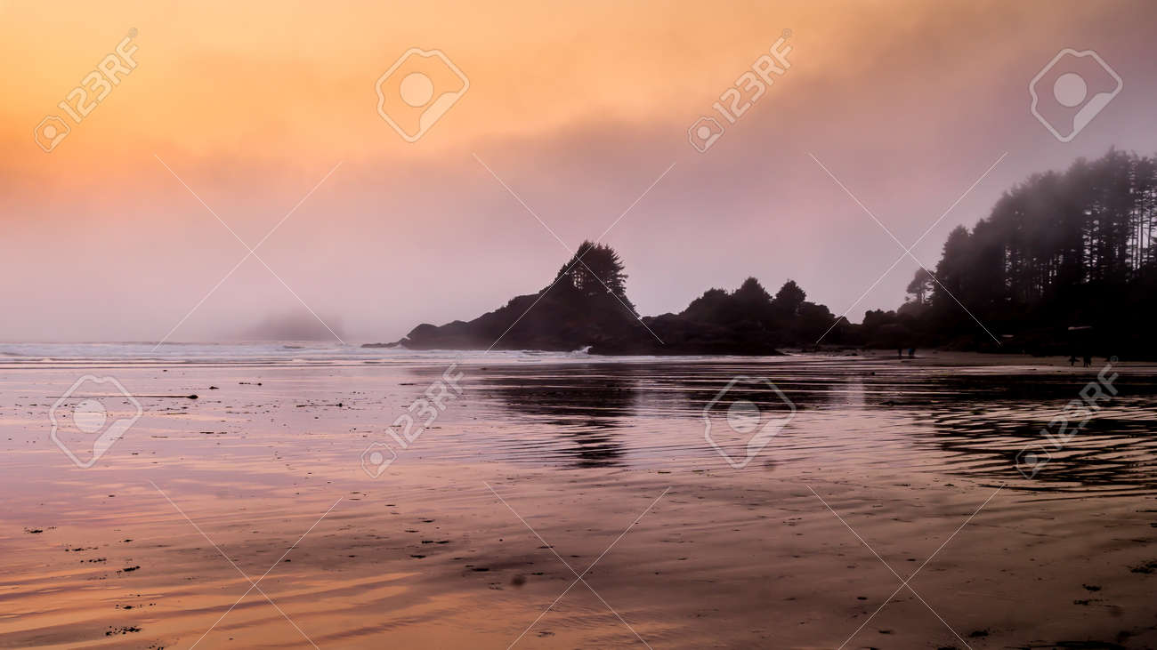 Sunset causing an Orange Glow over the Fog hanging over the rocky shore between Cox Bay and Chesterman Beach at the Pacific Rim National Park on Vancouver Island, British Columbia - 158541319