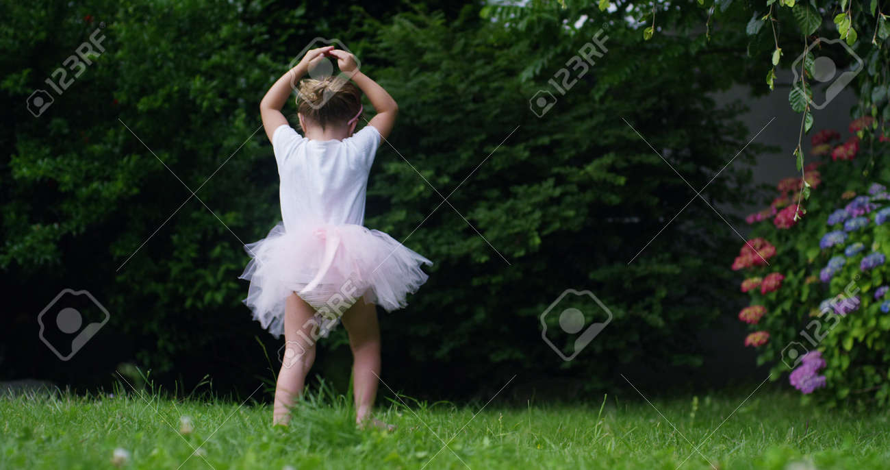 69473df2d On A Sunny Spring Day A Baby Girl Dressed As A Dancer Plays Tries ...