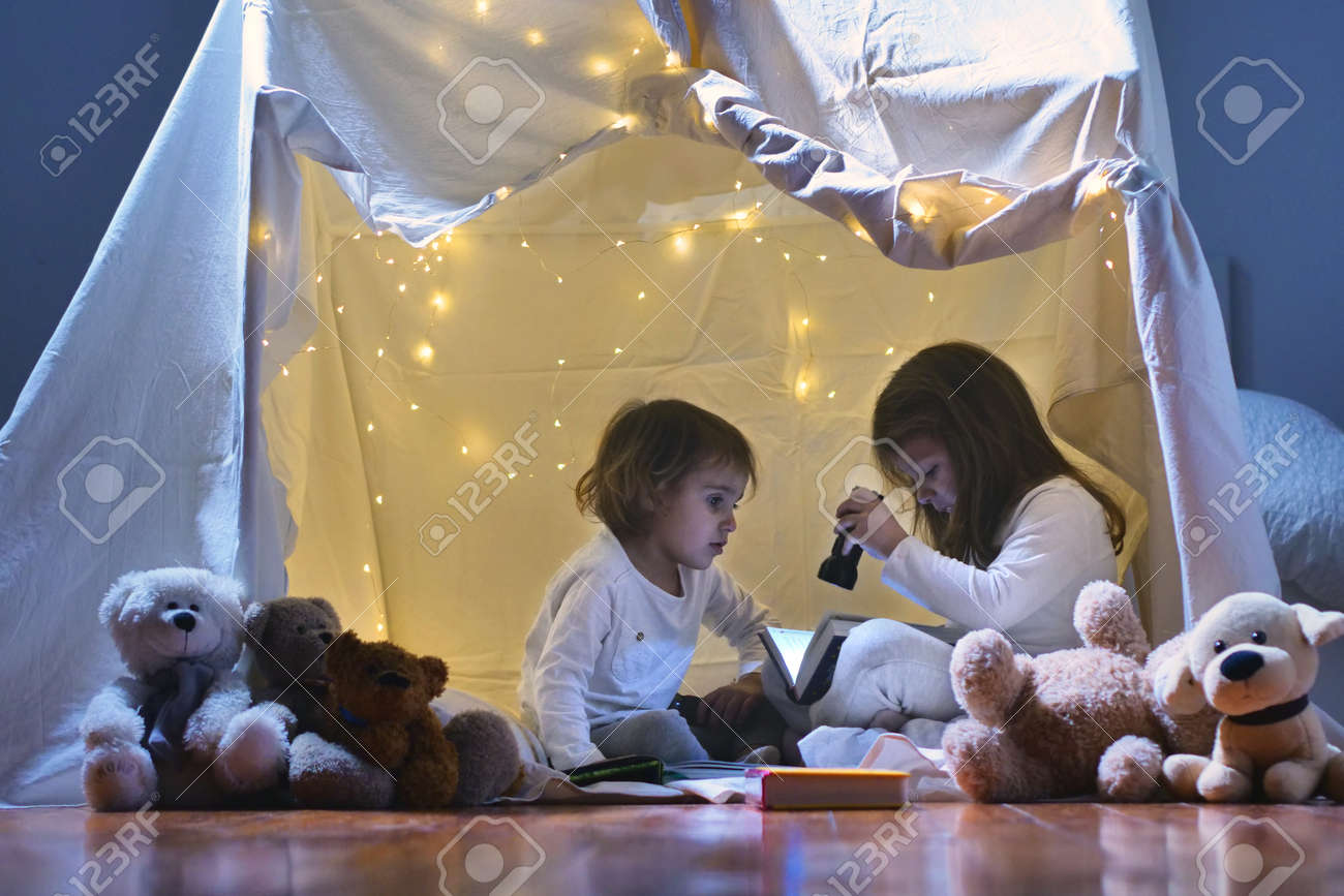Two girls play at home in the evening to build a tent to read