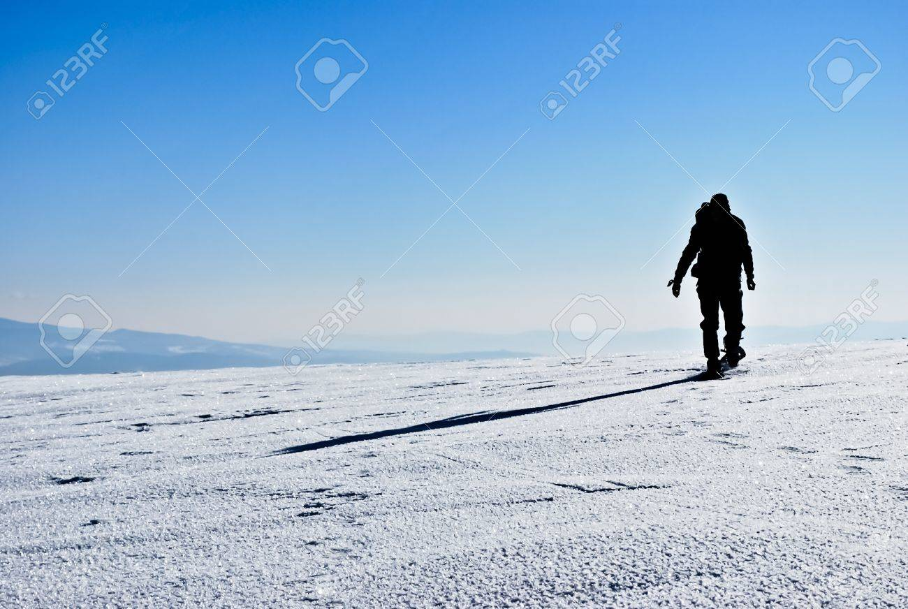 Silhouette and shadow of hiker running on snowy mountain ridge Stock Photo - 8419676