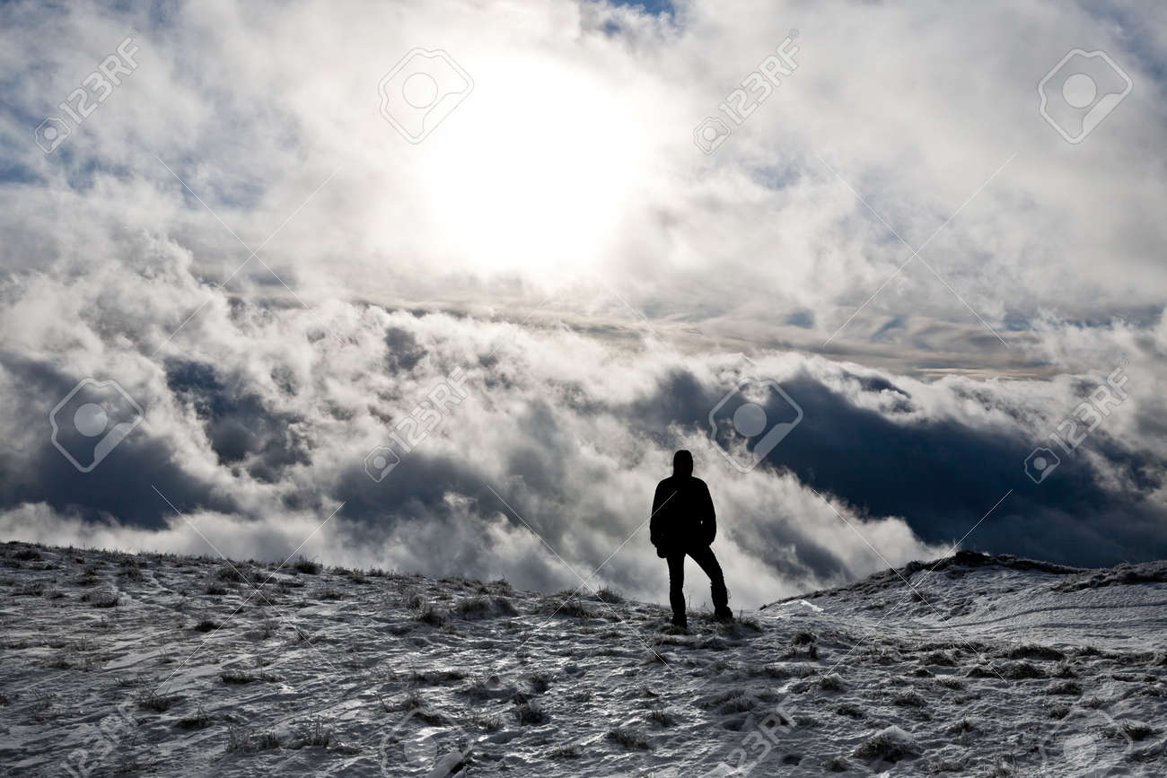 Silhouette of a man standing on top of a hill with dramatic clouds as background Stock Photo - 17626987