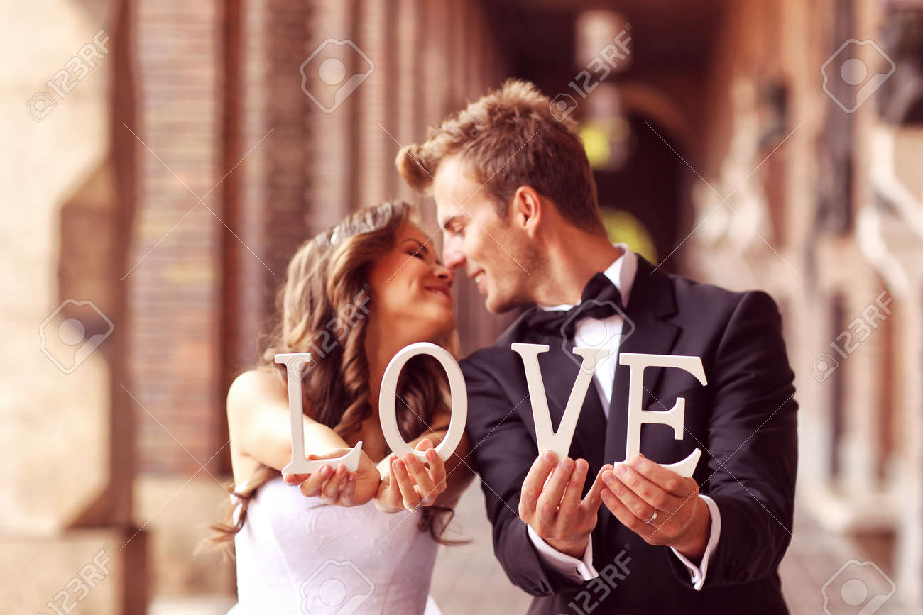 Beautiful bride and groom kissing and holding LOVE letters Stock Photo - 45822623