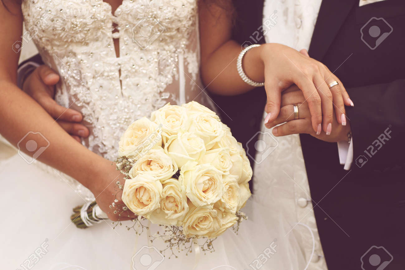 Beautiful bride and groom with bouquet on wedding day holding hands beautiful bride and groom with bouquet on wedding day holding hands imagens 46222600 junglespirit Images
