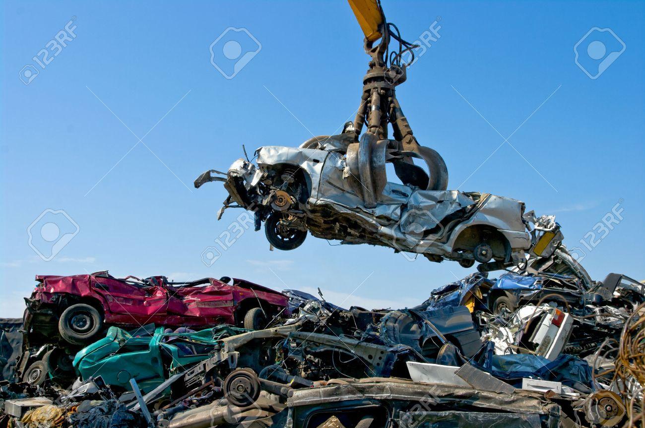 Crane picking up a car in a junkyard - 24960367