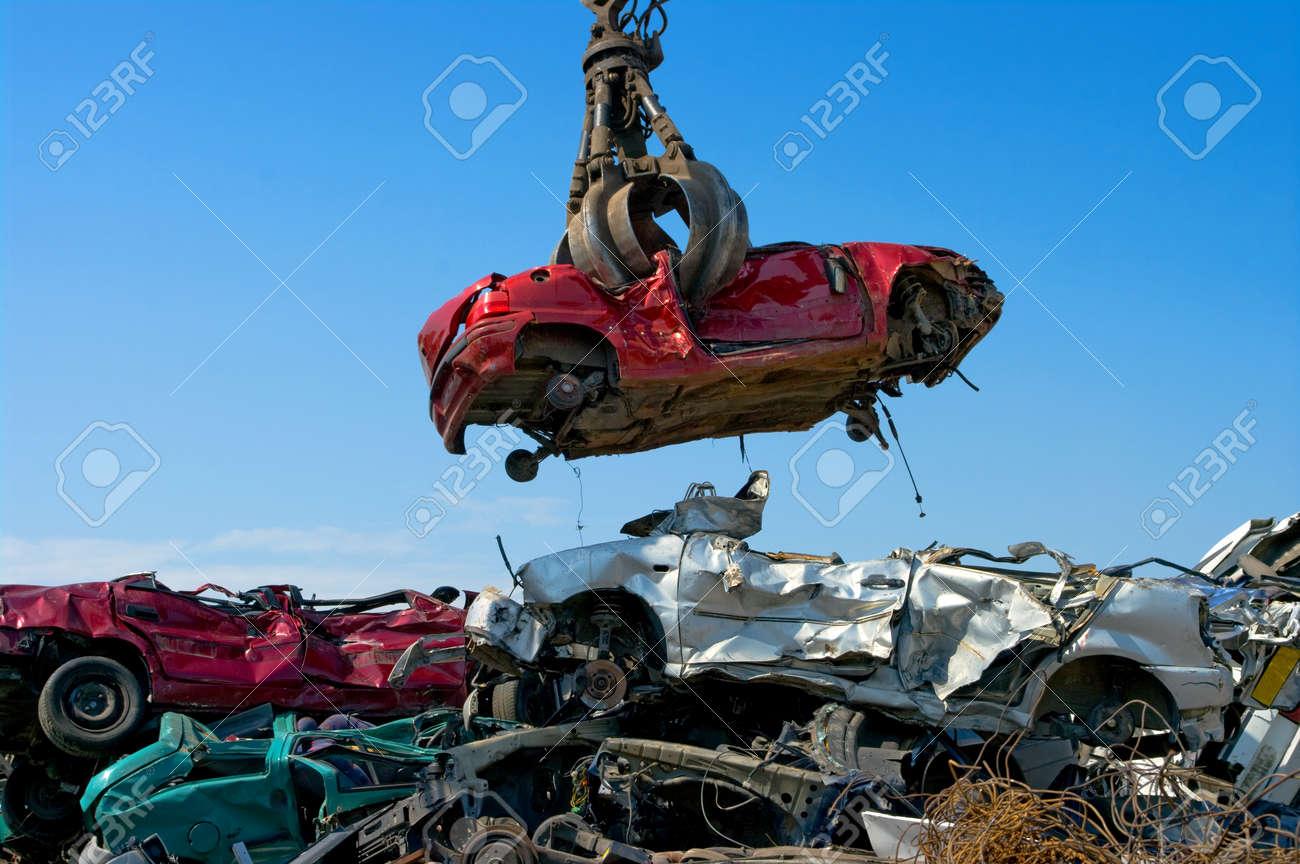 Crane picking up a car in a junkyard - 24981826