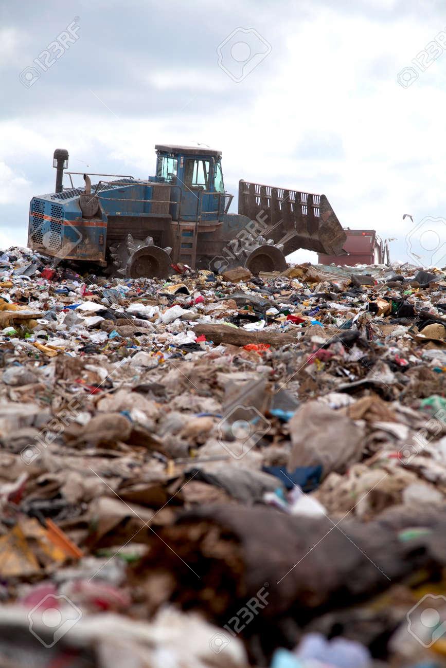 Truck flattening trash in landfill - 25569944