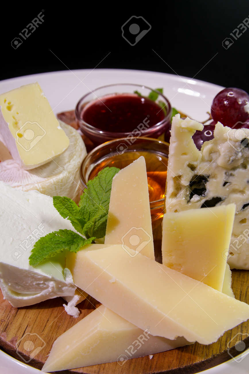 Cheeseboard. Parmesan, blue cheese, Camembert served with mint, honey, jam, grapes on a wooden board - 142255462