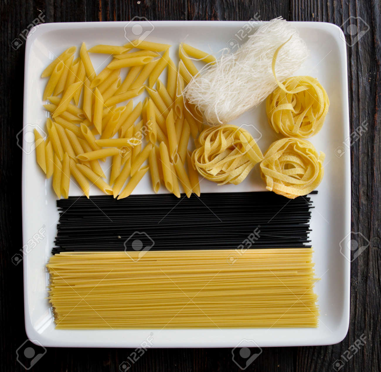 Close up of square white plate with various types of dry pasta.Dark wooden background - 142255463