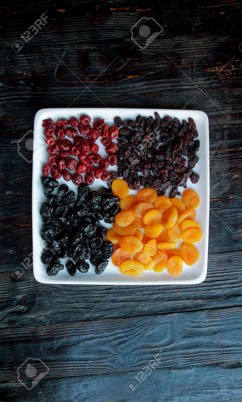 Dried fruits on a dark wooden background.Raisins, dried apricots, prunes, dried cherries on a square white plate.Copy space - 142255469