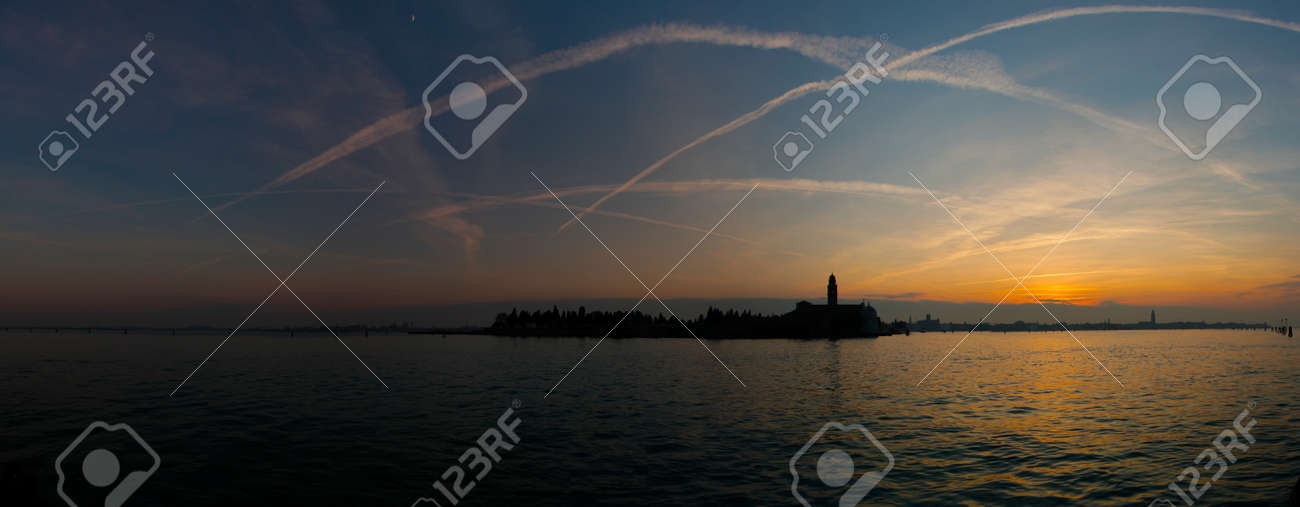 View of the San Michele island in Venice at sunset.Traces of airplanes in the sky. - 142552195