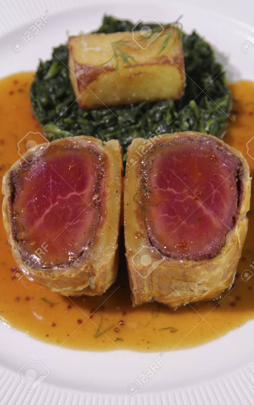 Slice of Beef Wellington with Spinach and fried potatoes. - 142631910