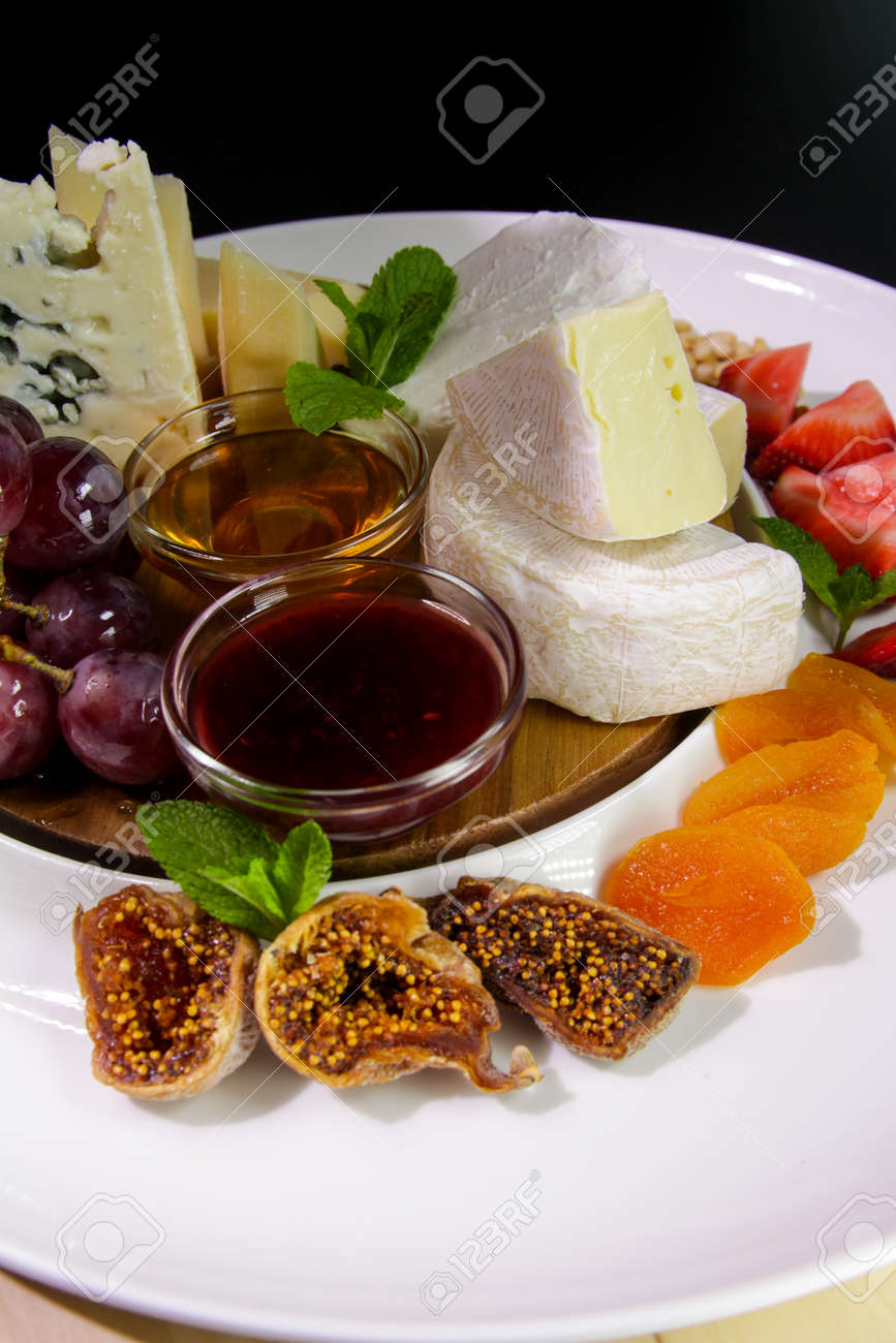 Cheese plate. Camembert cheese, Parmesan, blue cheese served with grapes, mint, jam, figs, honey, strawberries, dried apricots on a white plate. - 142921490