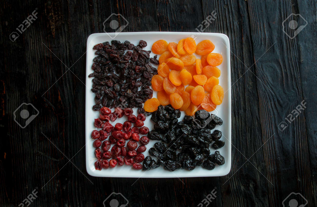 Dried fruits on a dark wooden background.Dried apricots, prunes, raisins, dried cherries on a square white plate.Copy space. - 141098579