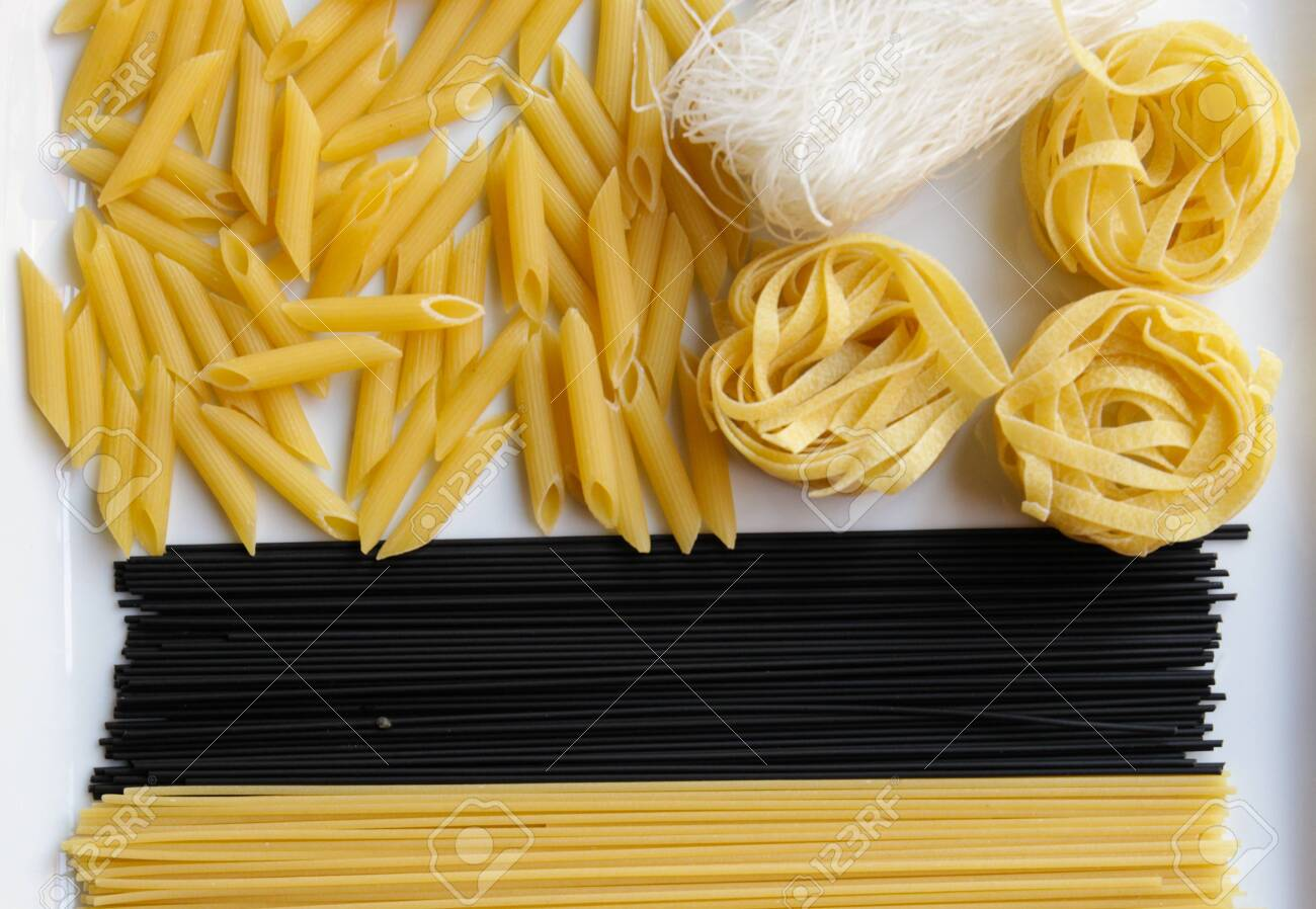 Close up of various types of dry pasta.Penne, spaghetti, noodles, black spaghetti, fettuccine, funchoz. - 141098622