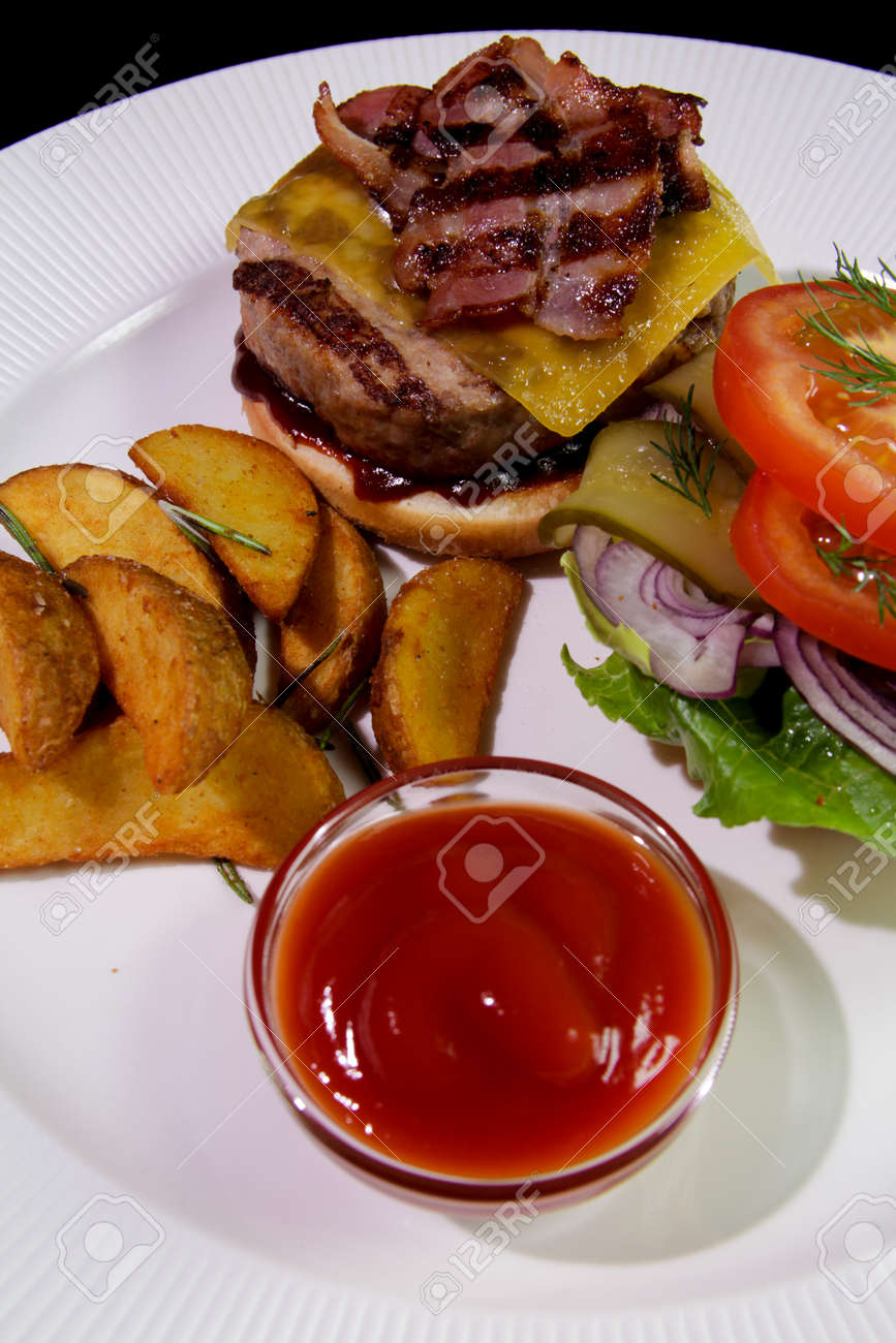 Burger with fried bacon, french fries, vegetables and ketchup on a white plate.Close-up.Energy-dense food. - 141098630