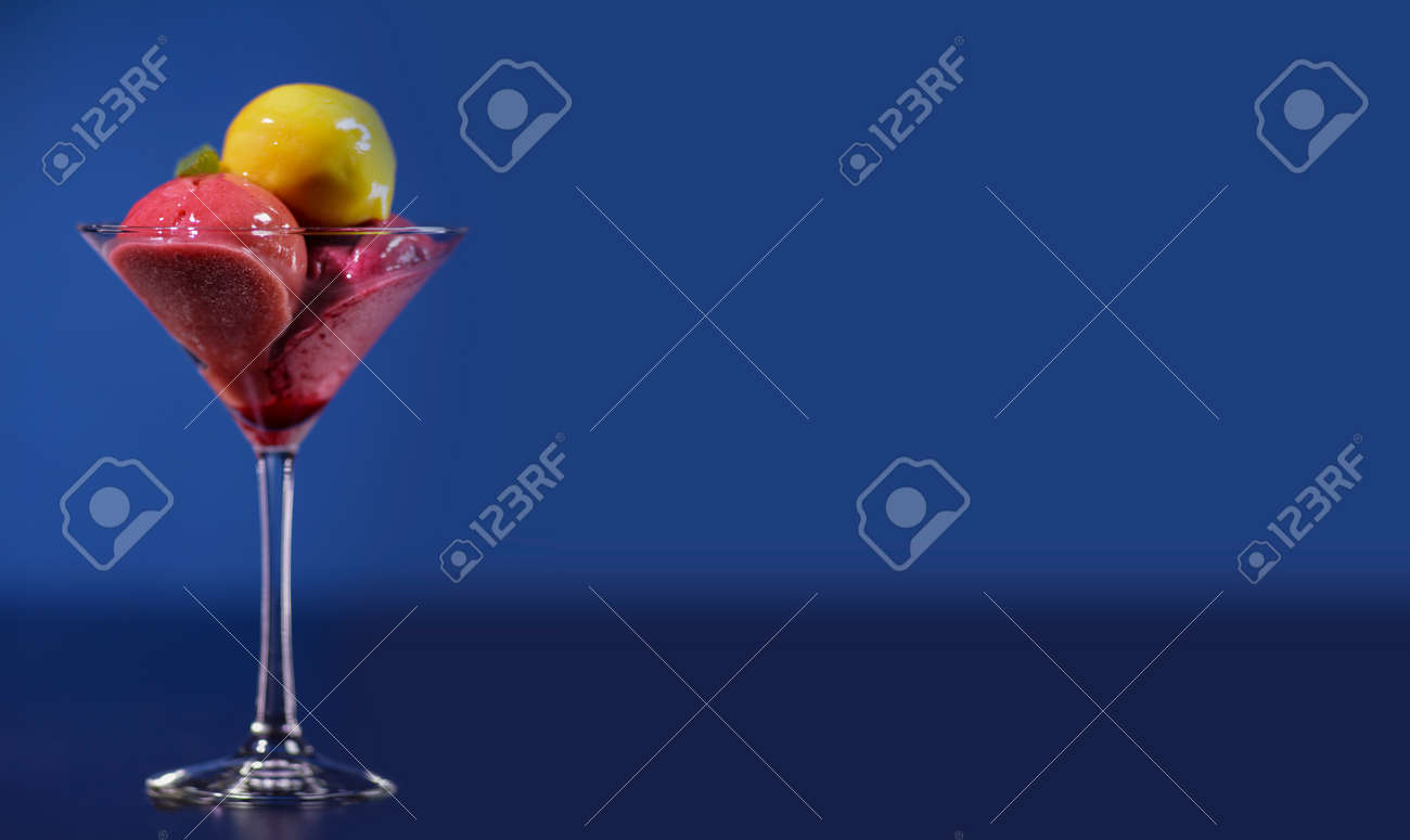 Yellow and red ice cream balls in a glass canister. Isolated against a blue background.Panorama for banners.Copy spase. - 142921489