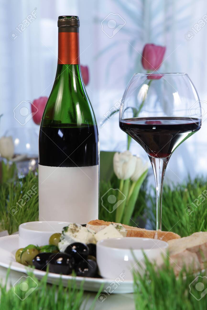 A bottle of red wine and a glass, a cheese plate with brie cheese, olives.Copy space. - 144390698