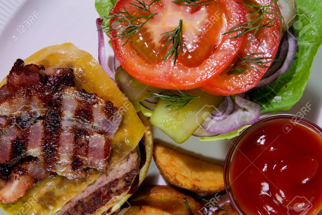 Burger with fried bacon, french fries, vegetables and ketchup on a white plate. - 144390712