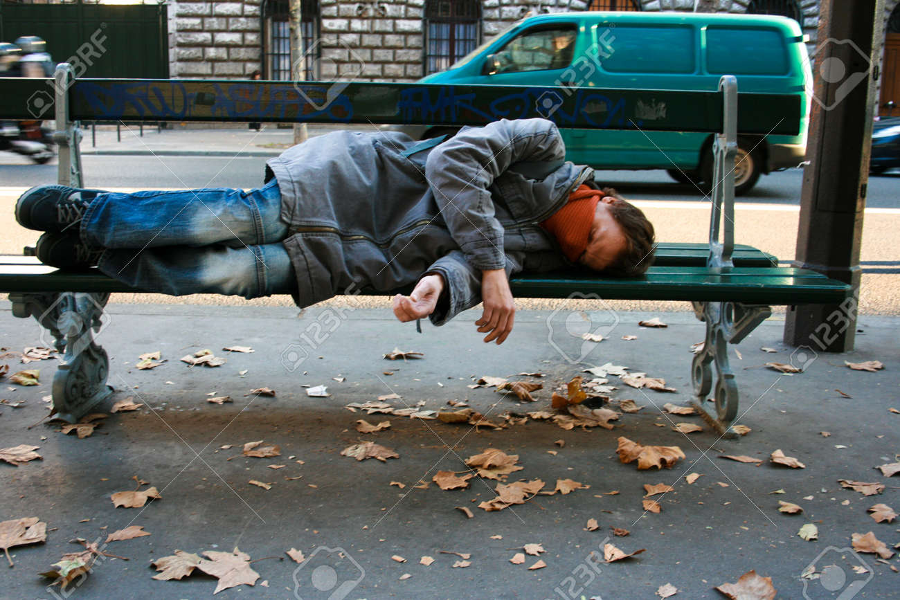 Drunk young man sleeping on a bench on the street. Autumn leaves on the pavement, traffic in the background. - 144593850