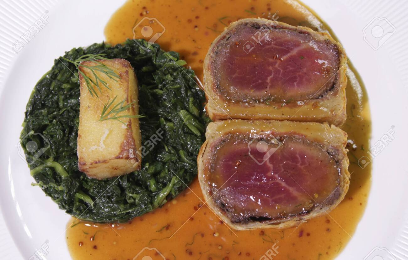 Carved Beef Wellington with Spinach and fried potatoes. - 144390485