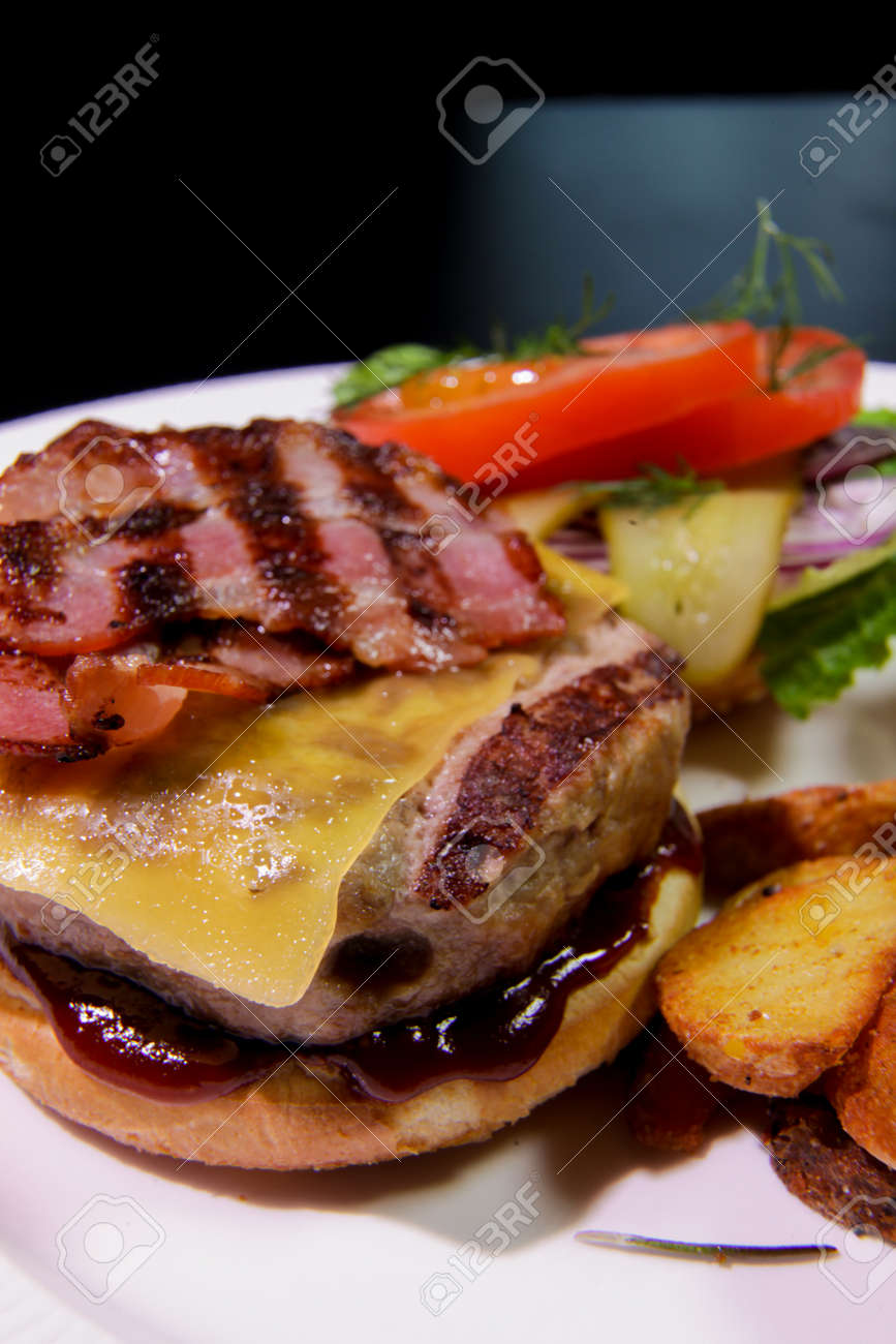 Close-up of Burger with fried bacon, french fries, vegetables and ketchup on a white plate - 144390489