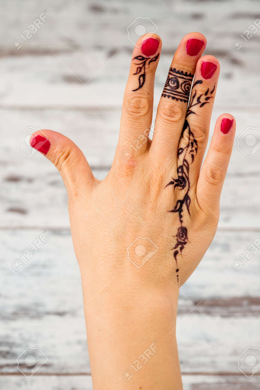 Woman Hand With Nail Polish Painted With Black Henna Counting