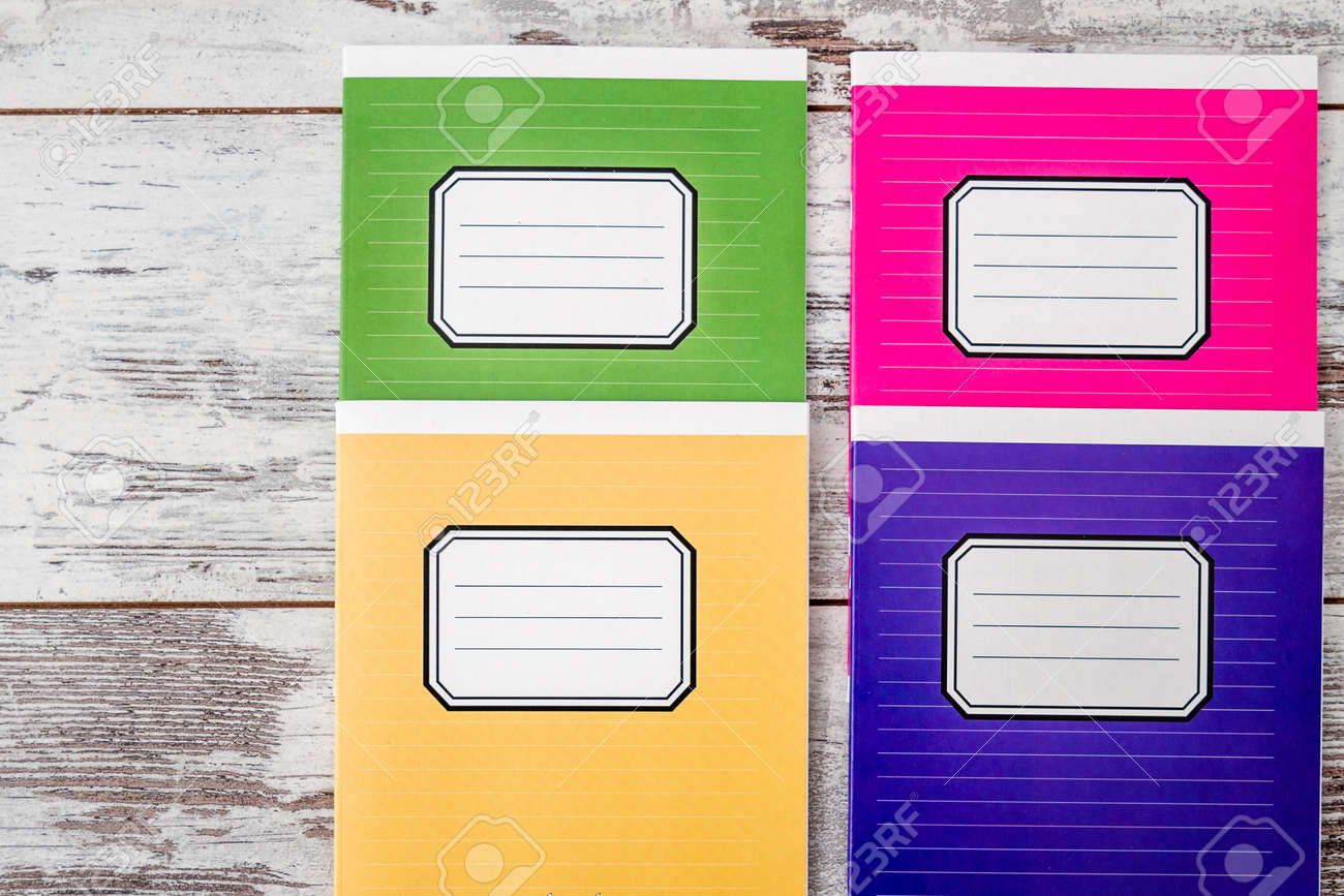 colorful notebooks with name label on cover on white wooden