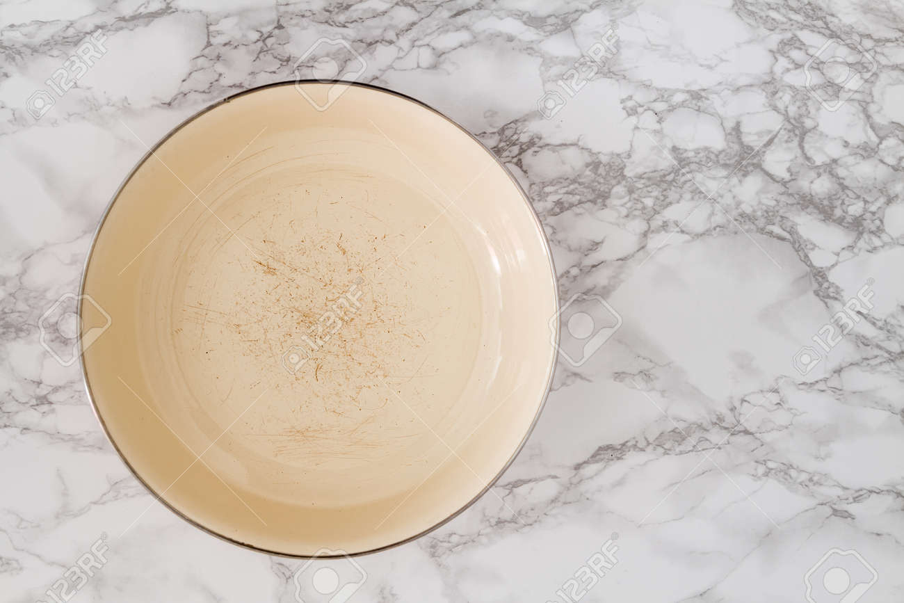 inside of worn out yellow vintage enamel plate on white marble