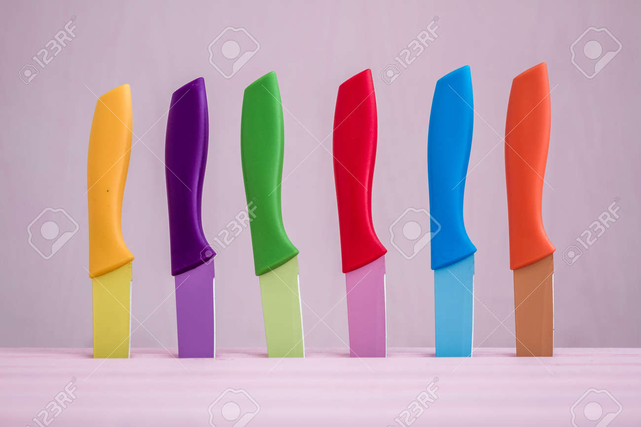 Set of Colorful Kitchen Knives over pink background