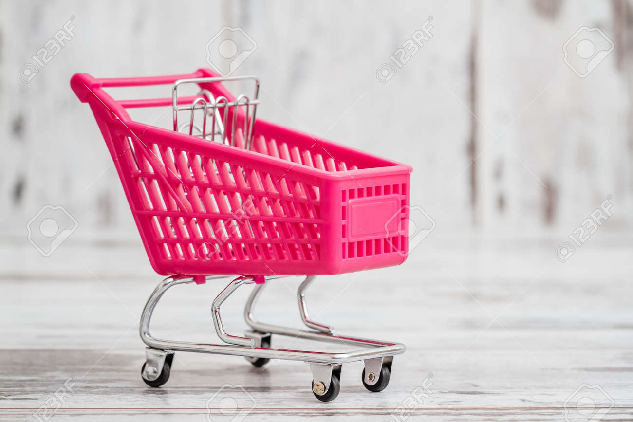 Miniature Pink Toy Shopping Cart On White Wooden Background