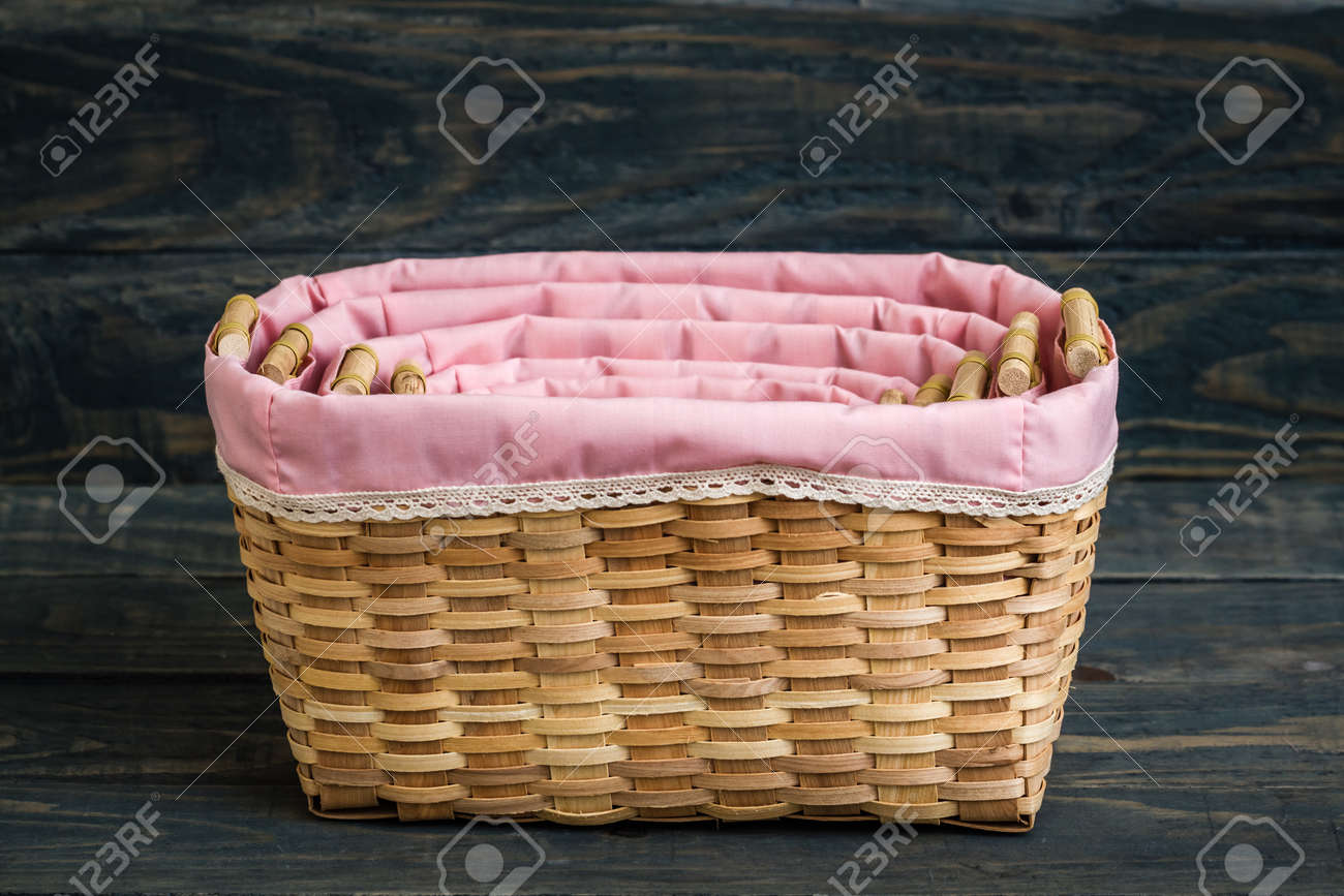 Decorative rattan baskets with pink lining fabric on gray wooden