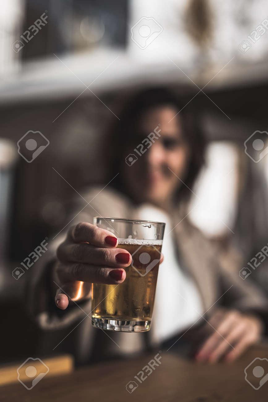 Mujer De 40 Años Bebiendo Cerveza En La Terraza De Un Bar Retroiluminado
