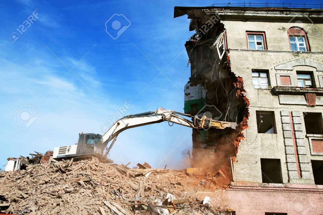 excavator demolishing a brick building. Machinery Demolishing Building. - 159545329