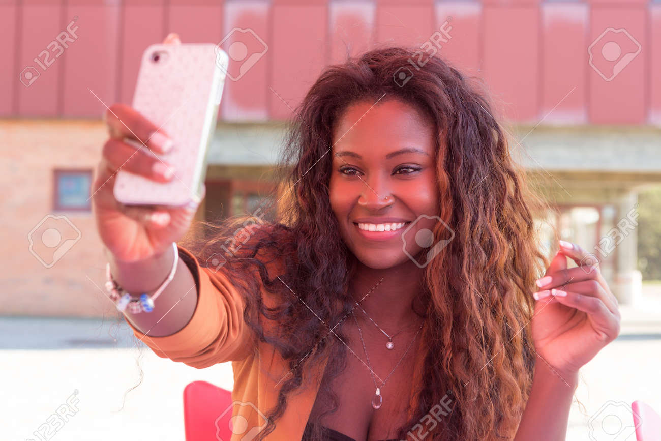 young african student making a pause to take a selfie stock photo