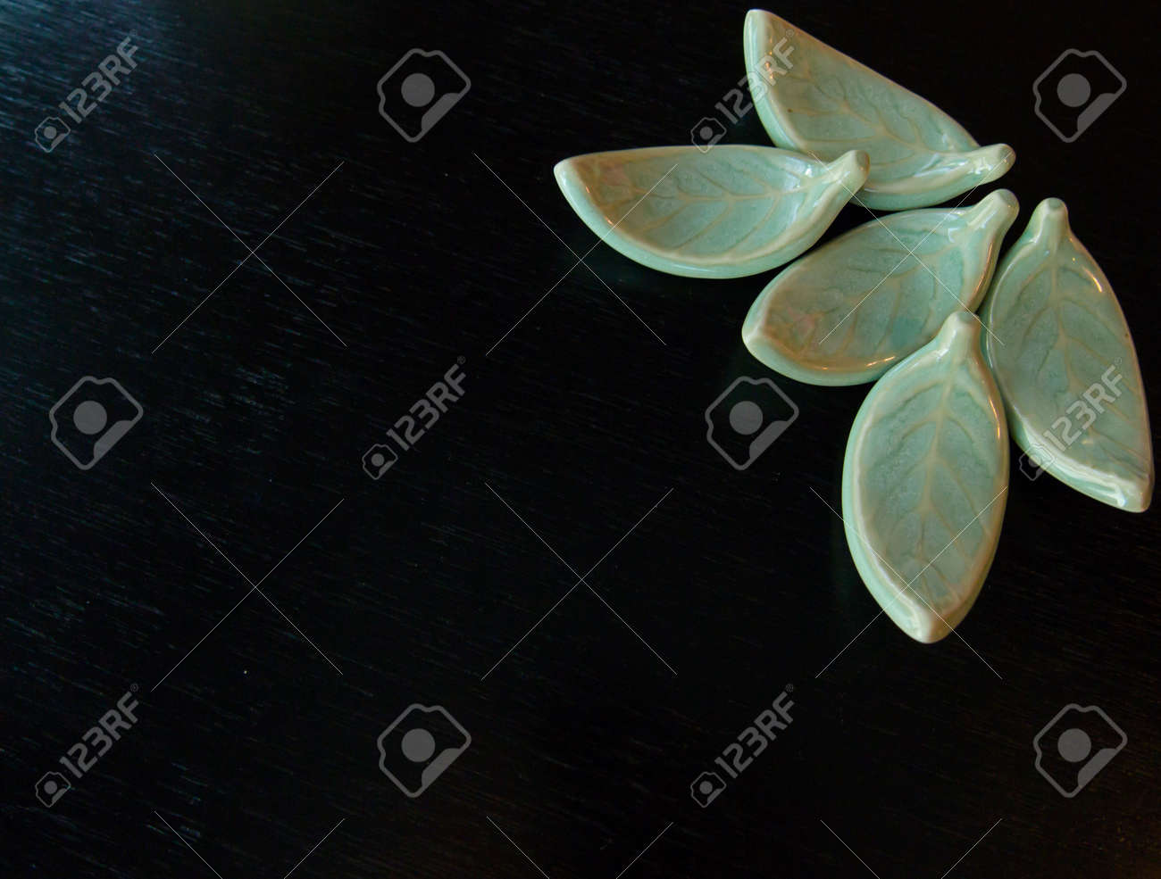 Ceramic leaves arrange on black table Stock Photo - 21740139