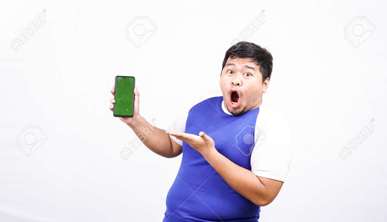 funny asian man with green screen phone isolated white background - 163014210