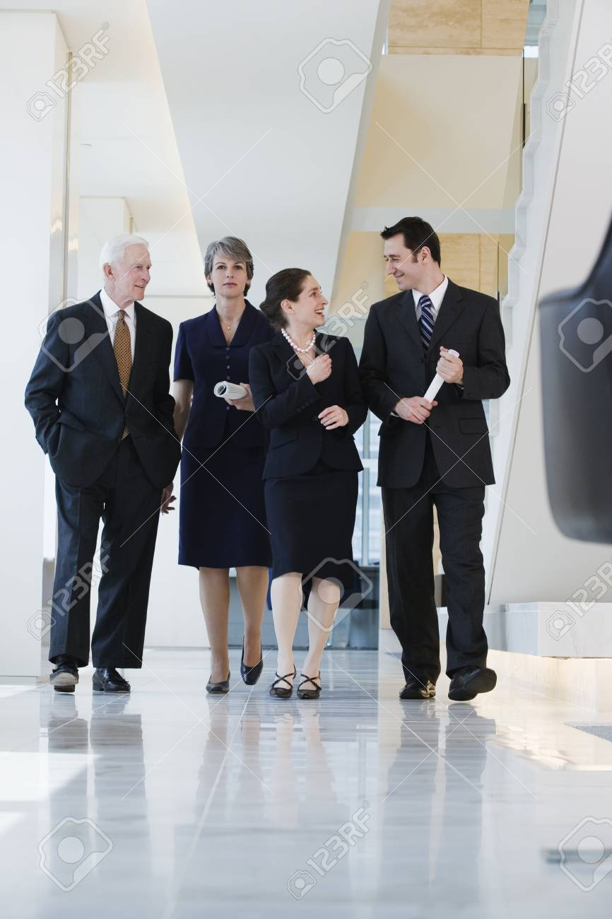 View of four businesspeople walking in a corridor deep in conversation. Stock Photo - 5579462