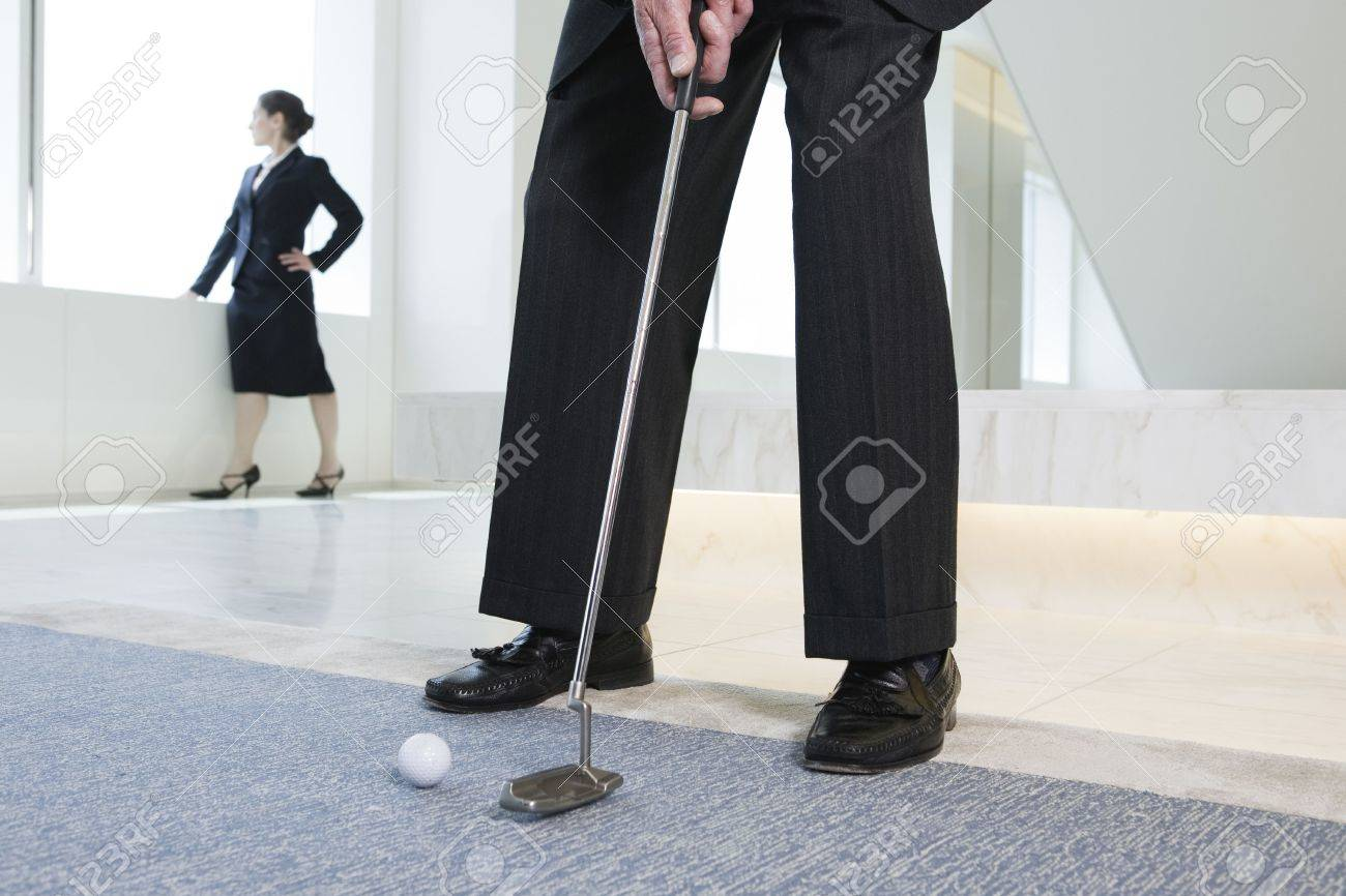 View of businessman playing golf with woman standing in background. Stock Photo - 5579483