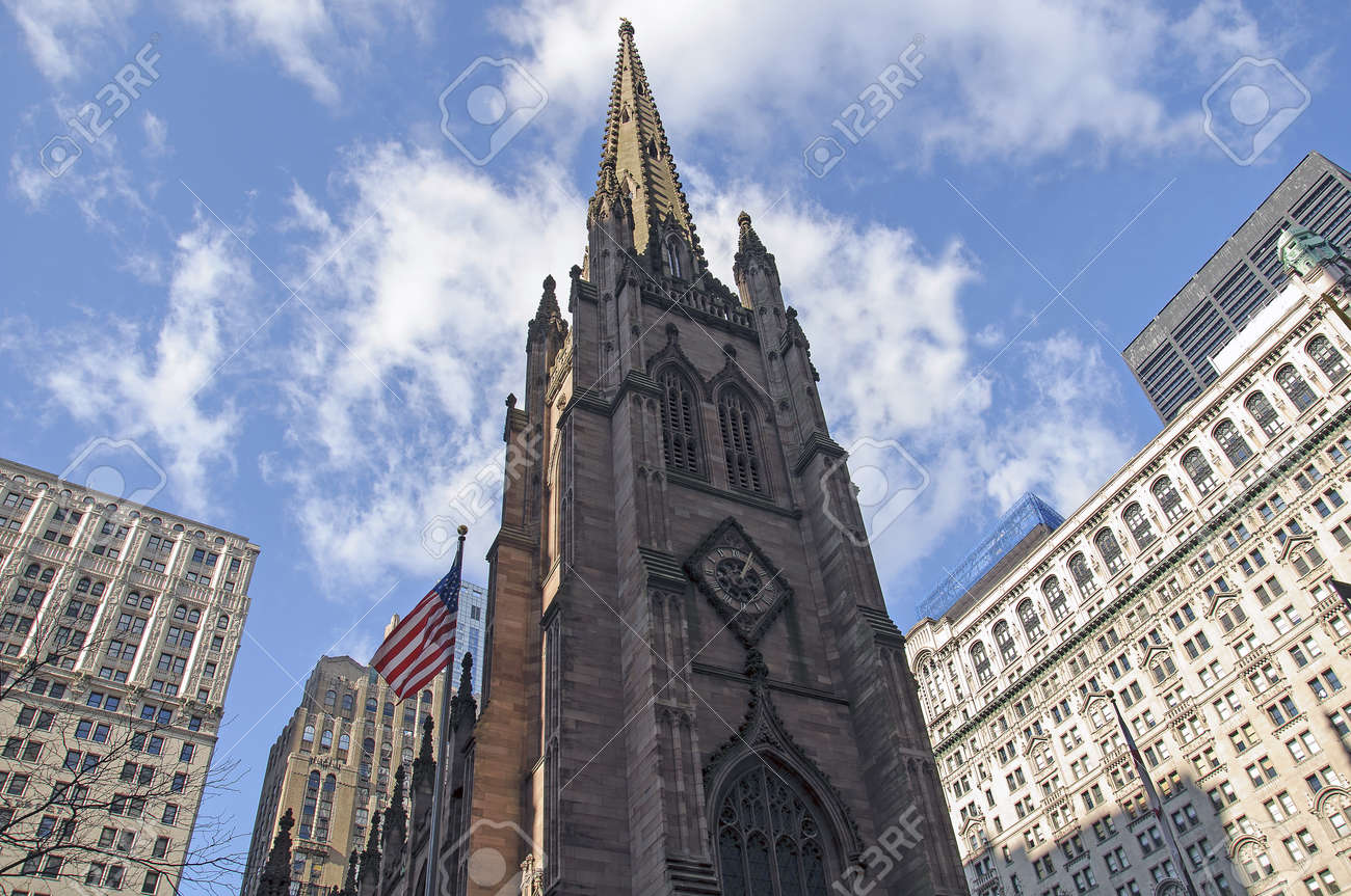 old church in new york city rounded by big buildings stock photo