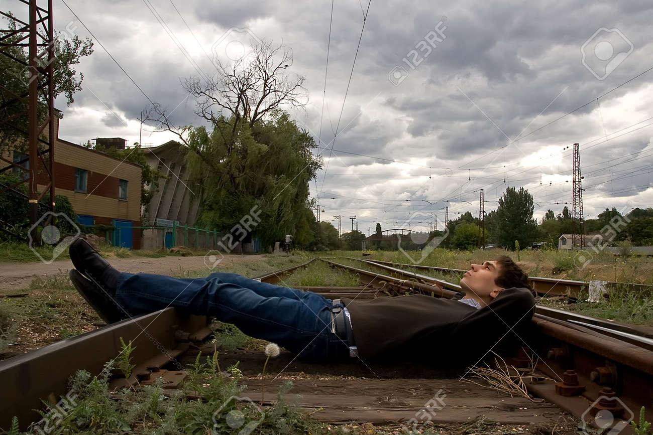 Young man laying on a railway tracks looking into the sky Stock Photo - 5647504