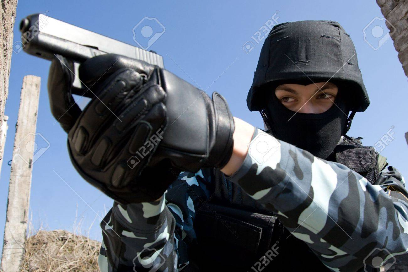 Soldier in full ammunition aiming the target with a semi-automatic