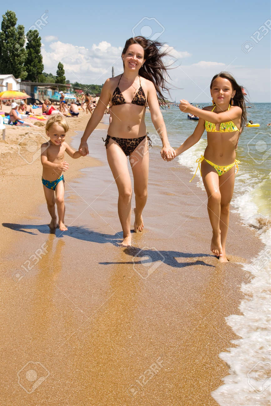 Mom and her children enjoying their vacation at the crowded beach Stock Photo - 7336157
