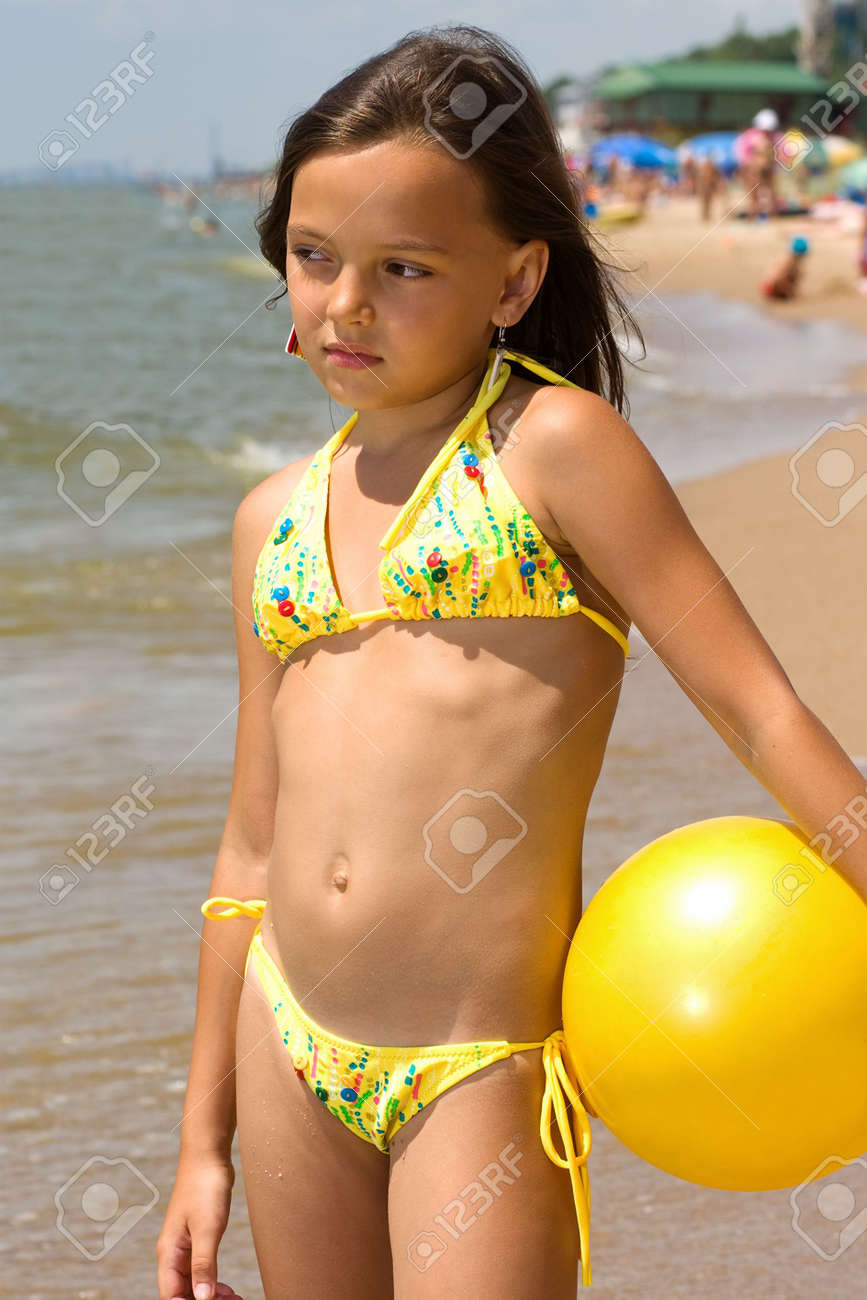d79f4ac40e Small girl standing with a ball at the shore of a sea Stock Photo - 7357081