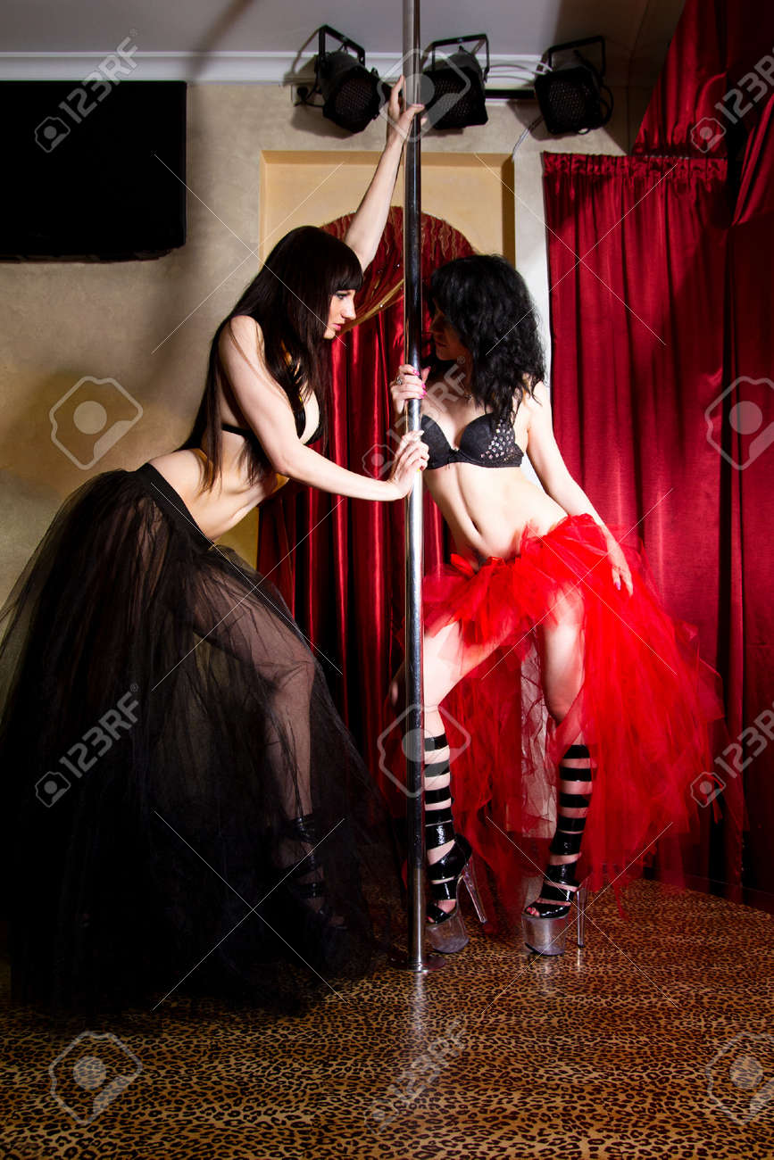 Two young attractive women in lingerie and high heels pole dancing in the adult entertainment club Stock Photo - 9691129